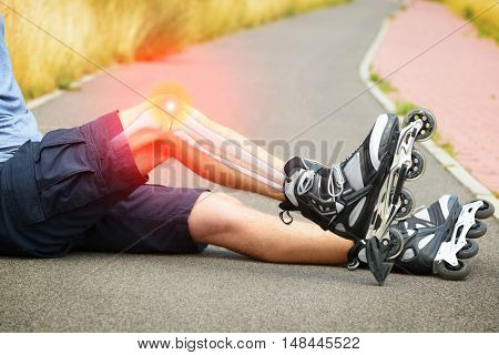 Injured skater sitting with his painful leg