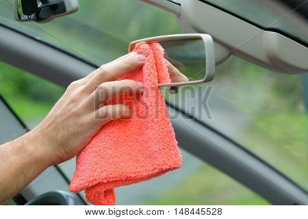 Hand with cloth cleaning car interior