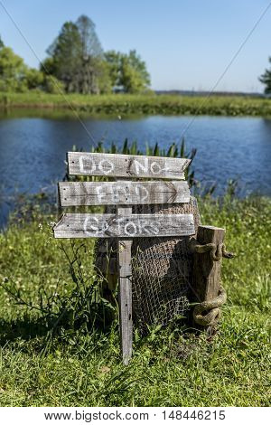 'Do not feed that Gators' wooden sign post, beside a lake in the American deep south poster