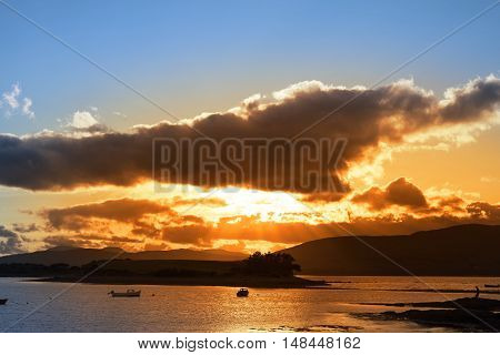 boats in a quiet bay with island near kenmare on the wild atlantic way ireland with an red sunset