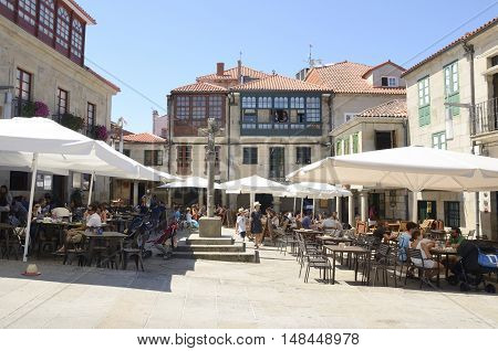 PONTEVEDRA, SPAIN - AUGUST 6, 2016: People at outdoor bars in Plaza of Stone in the city of Pontevedra Galicia Spain.