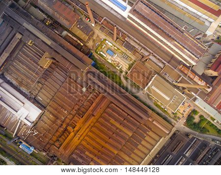 Aerial view of steelworks with rusty roofs. Heavy industry from above. Industrial background.