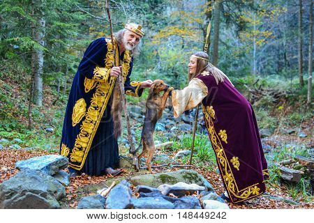 The old king a queen having funwith small hunting dog outdoors in colourful autumn forest