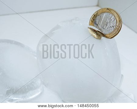 Cache euro coins in ice. Isolated on white background.
