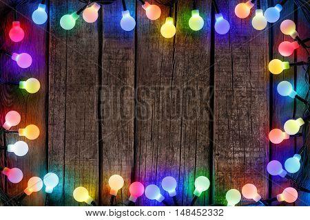Frame Of Colorful Christmas lights Bulb On Wood