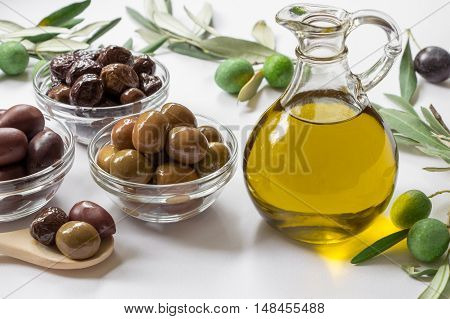 Glass bottle with premium virgin olive oil near variety of olives in bowls and spoon, olive tree branches on the white background. Premium virgin olive in bottle and variety of olives. Horizontal.