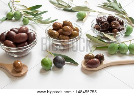 Olives black, green, sun-dried into a bowls next to the olive tree branches, two wooden spoons with olives on the white background. Three types of olives. Horizontal. Daylight.