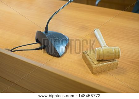 Clean wooden table in court of law with microphone and gavel, focus on gavel.