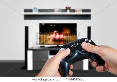Hands hold the game controller. Man playing a car racing on TV in a modern room