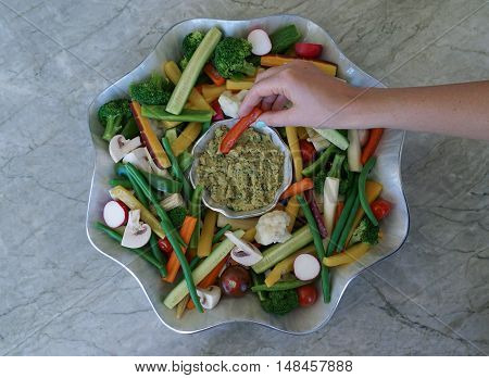 Vegetable Crudites and Dip/ vegetable platter on wood background, woman snacking, healthy eating, selective focus