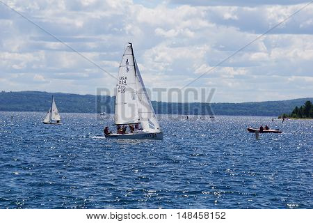 HARBOR SPRINGS, MICHIGAN / UNITED STATES - AUGUST 1, 2016: People enjoy a sailing lesson, provided by Little Traverse Sailors, off the shore of Harbor Springs.