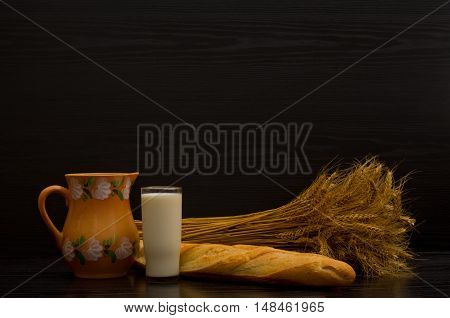 Jug glass of milk white bread and a sheaf on a black background with space for text