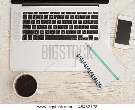 Top view of a laptop keyboard smart phone a notebook with a pencil and a cup of coffee