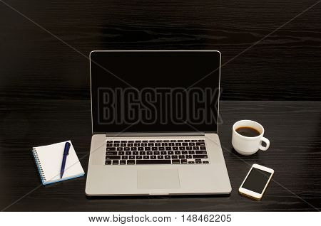 Open the laptop mug of coffee notepad and telephone on a black background