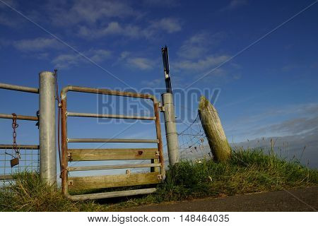 Metal gate on a dike under blue sky