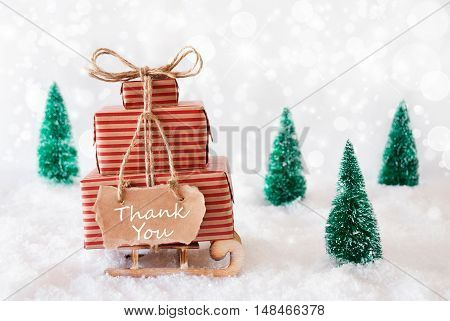 Sled With Christmas Gifts Or Presents. Snowy Scenery With Snow And Trees. White Sparkling Background With Bokeh Effect. Label With English Text Thank You