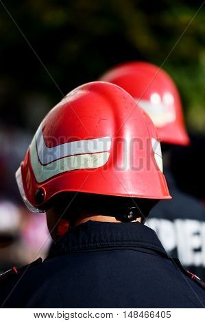 Firefighters wearing firefighter helmets are seen from behind