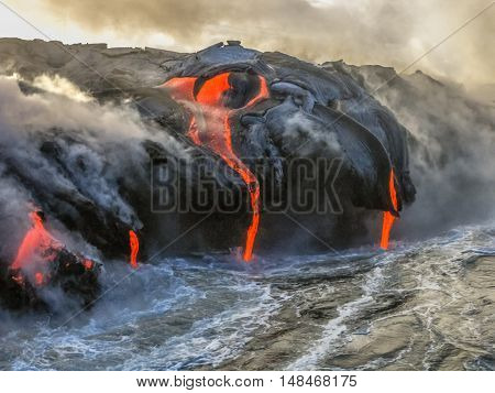 Kilauea Volcano in Hawaii Volcanoes National Park, also known Kilauea Smile because from 2016 seems to smile, erupting lava into Pacific Ocean, Big Island. Scenic sea view by boat.