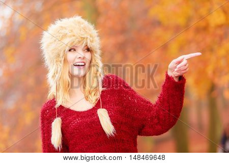 Pretty Smiling Woman In Fur Winter Hat Pointing.