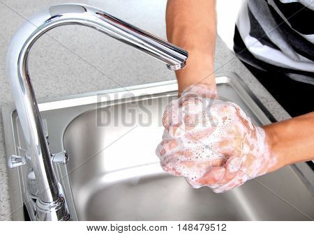 man with soapy hands in the kitchen