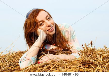 Young girl is resting on hay against light sky background at stroll time in summer