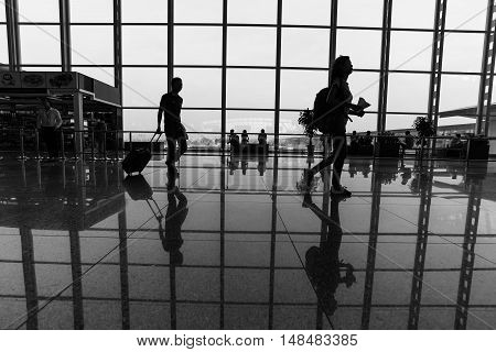Travelers walk through an airport terminalSilhouette traveler woman and passenger In the airport