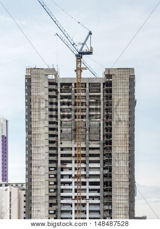 Modern high building in under construction with high cran in the urban area.