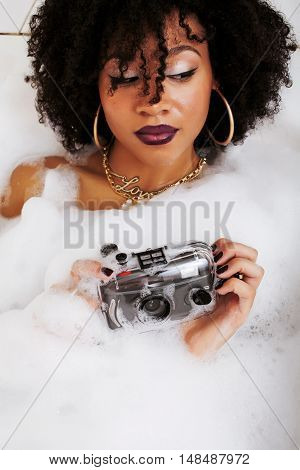 young afro-american teen girl laying in bath with foam, wearing swag jewelry flawless, making selfie close up