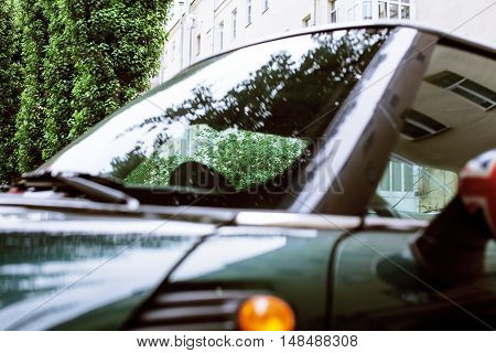 vintage car detail, concept of British Patriotism shown as flag on mirror, trees in reflection windshield, body part close up, focus on tree