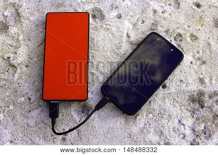 Magenta pink powerbank and smartphone on concrete background top view