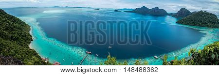 Panorama view from the peak of Bohey Dulang Island,Sabah,Borneo.Mirror smooth ocean surrounded by mountains.The bright blue water and rocky shore in the tropical island of Semporna,Sabah,Borneo.
