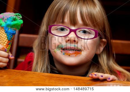 A little girl with a messy and colorful ice cream cone smiles at the camera with a messy face. She has glasses and purple finger nails.