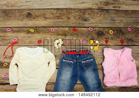 Children's clothing and accessories: jeans, blouse, vest, hair clips, necklace and bracelet on old wooden background. Top view.