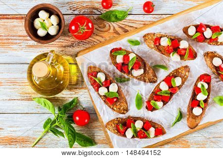 bruschetta with tomatoes mini mozzarella and basil leaves on fried on olive oil baguette with seeds served on chopping board on parchment paper bottle with oil tomato and herbs on wooden background view from above