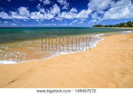 The popular Sunset Beach, North Shore, Oahu, Hawaii, in the summer when the sea is calm and flat. Sunset Beach is home of the World Cup of Surfing in winter with big waves 15 to 30 feet high.