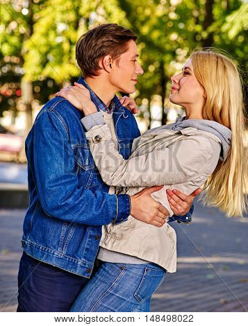 Young couple in love hugging and flirting in park and looking each other with love in autumn park. Romantic love in autumn park.