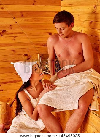 Happy couple in love relaxing at sauna. Rest in sauna. Wooden hot sauna.