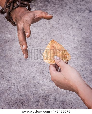 Hand holding food and give for slave are starving.