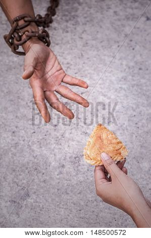 Hand holding food and standing for slave are starving.