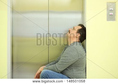 The sad man in glasses with a mustache sitting about the elevator