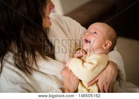 Mother in bathrobe holding he little smiling baby