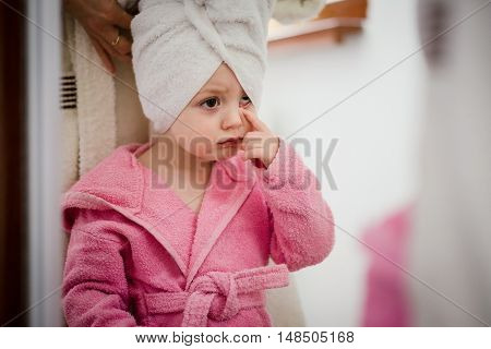 Worried little child in bathrobe and towel on head looking to the mirror