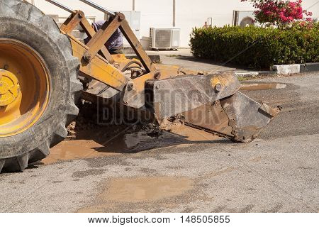 Excavator bulldozer work a dig hole the repair of pipe water and sewerage on road
