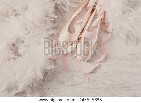 Pastel pink ballet shoes background. New pointe shoes with satin ribbon lay on white rustic shubby chic wood near feather boa, top view with copy space