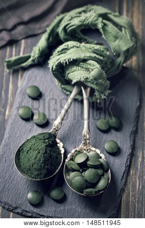 Spoons with spirulina pills and powder