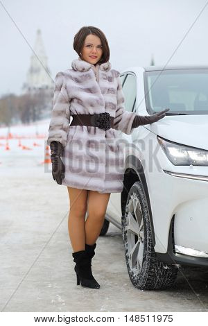 MOSCOW - FEB 14, 2015: Beautiful girl (with model release) in a fur standing near the white car on a test drive in Kolomenskoye