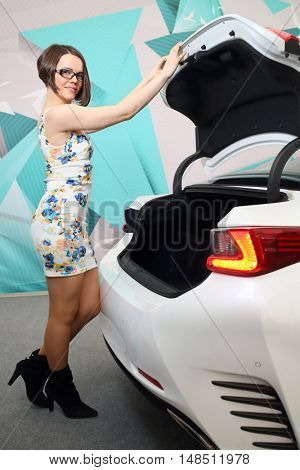 MOSCOW - FEB 14, 2015: Beautiful brunette (with model release) in glasses and dress opening white trunk of a car on Russian sixth test drive Lexus Master Class