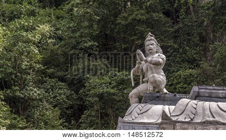 The roof of a Hindu temple, with Hanuman, the Hindu monkey god, in the foreground and lush foliage in the background