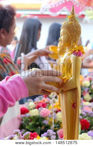 water pouring to Buddha statue in Songkran festival tradition of thailand
