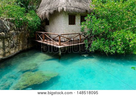 House with thatched roof in a safe Harbor with clear blue waters